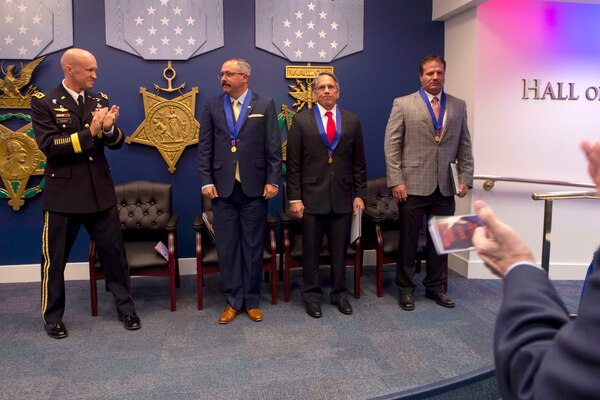 Left to right: Army Lt. Gen. Darsie Rogers, Defense Threat Reduction Agency deputy director for combat support, applauds after awarding the Medal of Valor to Michael Anthony Dunne, William Timothy Nix and Brandon Ray Seabolt at the Pentagon, Aug. 14, 2018. The men, retired military special operators, were recognized for their actions against an armed enemy while serving as civilian contractors in Afghanistan. DoD photo by Navy Petty Officer 2nd Class Everett Allen
