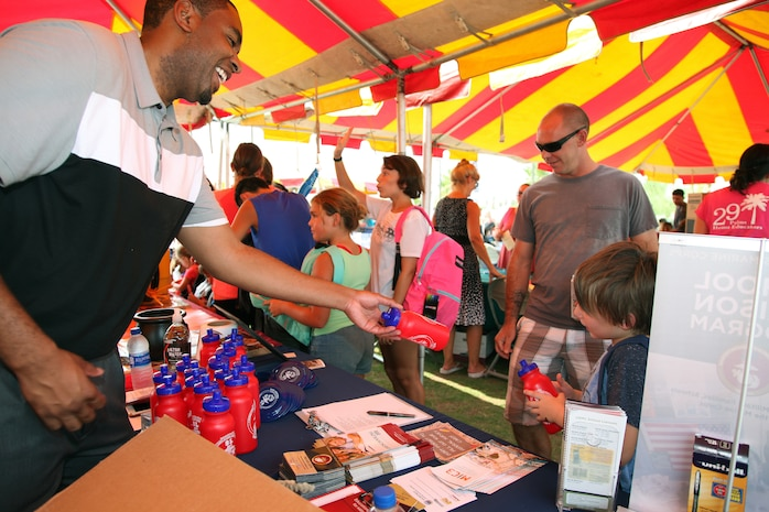 Walter Parham, School Liaison, hands out water bottles to family members during the Back to School Bash at Victory Field, Marine Corps Air Ground Combat Center, Twentynine Palms, Calif., Aug. 10, 2018. About 1,500 attended the event hosted by Marine Corps Community Services and the Combat Center School Liaison. (Marine Corps photo by Kelly O'Sullivan)