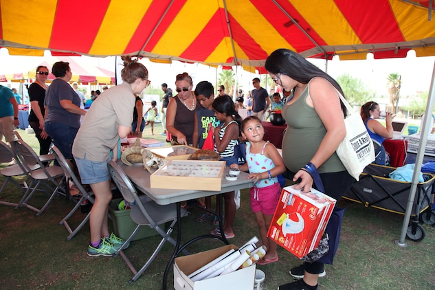 Family members crowd around the Environmental Affairs booth to learn about desert animals, insects and reptiles during the Back to School Bash at Victory Field, Marine Corps Air Ground Combat Center, Twentynine Palms, Calif., Aug. 10, 2018. About 1,500 attended the event hosted by Marine Corps Community Services and the Combat Center School Liaison. (Marine Corps photos by Kelly O'Sullivan)