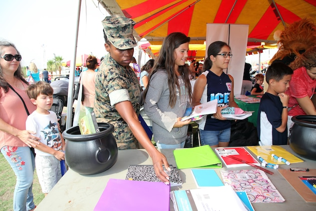 Staff Sgt. Rose Reed, Headquarters Company, Marine Corps Communication-Electronics School, Marine Corps Air Ground Combat Center, Twentynine Palms, Calif., picks up school supplies during the Back to School Bash at Victory Field, Aug. 10, 2018. About 1,500 attended the event hosted by Marine Corps Community Services and the Combat Center School Liaison. (Marine Corps photo by Kelly O'Sullivan)