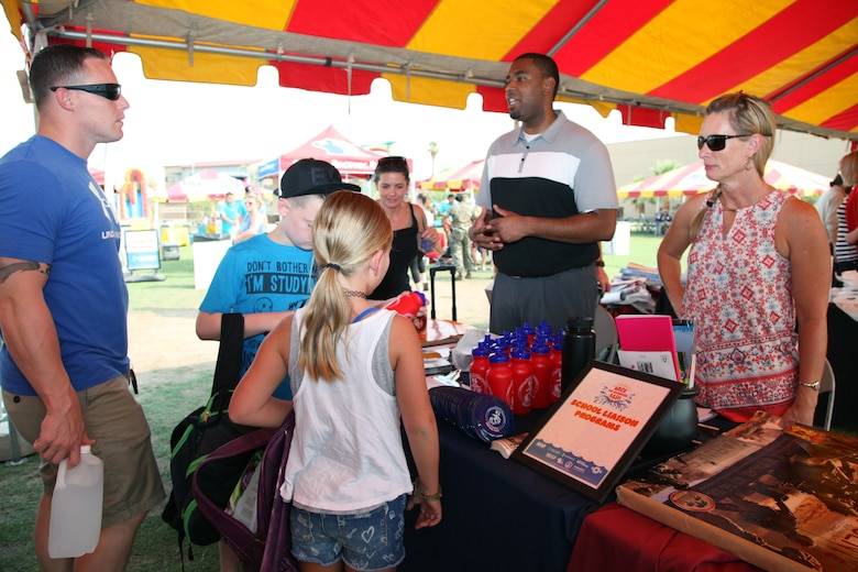 Walter Parham, School Liaison, center, and Kim Pope, Community Liaison, talk with family members during the Back to School Bash at Victory Field, Marine Corps Air Ground Combat Center, Twentynine Palms, Calif., Aug. 10, 2018. About 1,500 attended the event hosted by Marine Corps Community Services and the Combat Center School Liaison. (Marine Corps photo by Kelly O'Sullivan)