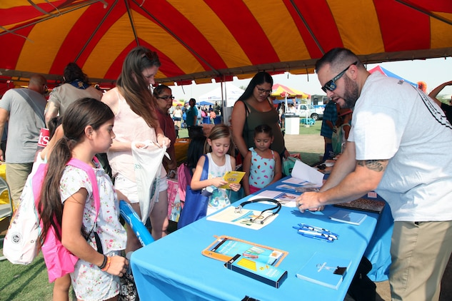 Chris Zamets of Brightwood College in Palm Springs hands out school supplies and information during the Back to School Bash at Victory Field, Marine Corps Air Ground Combat Center, Twentynine Palms, Calif., Aug. 10, 2018. About 1,500 attended the event hosted by Marine Corps Community Services and the Combat Center School Liaison. (Marine Corps photo by Kelly O'Sullivan)