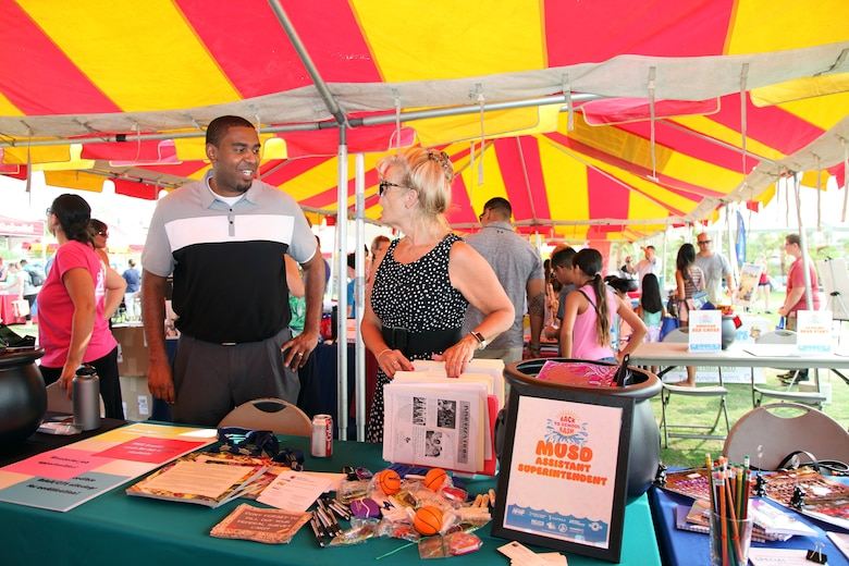 Walter Parham, School Liaison, left talks with Dr. Deborah Turner, Morongo Unified School District Assistant Superintendent of Instructional Services, during the Back to School Bash at Victory Field, Marine Corps Air Ground Combat Center, Twentynine Palms, Calif., Aug. 10, 2018. About 1,500 attended the event hosted by Marine Corps Community Services and the Combat Center School Liaison. (Marine Corps photo by Kelly O'Sullivan)