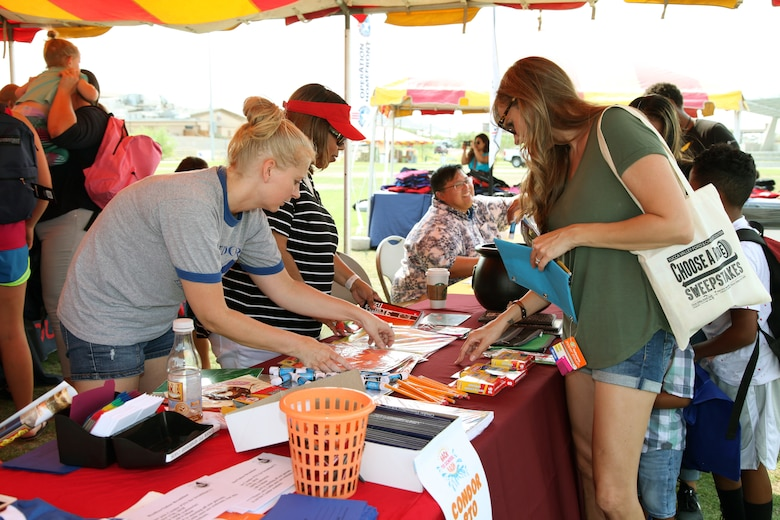 Family members peruse offerings during the Back to School Bash at Victory Field, Marine Corps Air Ground Combat Center, Twentynine Palms, Calif., Aug. 10, 2018. About 1,500 attended the event hosted by Marine Corps Community Services and the Combat Center School Liaison. (Marine Corps photo by Kelly O'Sullivan)