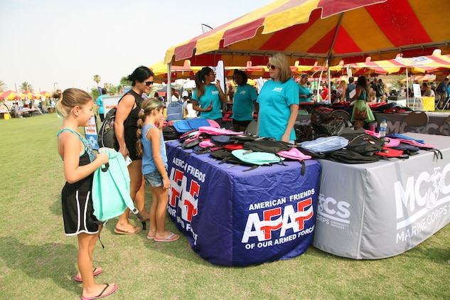 Kathryn Crank, right, Marine Corps Community Services Marketing Director, encourages young students to take a free backpack during the Back to School Bash at Victory Field, Marine Corps Air Ground Combat Center, Twentynine Palms, Calif., Aug. 10, 2018. About 1,500 attended the event sponsored by MCCS and the Combat Center School Liaison Office. (Marine Corps photo by Kelly O'Sullivan)