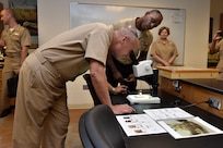 Vice Adm. Forrest Faison, Navy surgeon general and chief, U.S. Navy Bureau of Medicine and Surgery, looks through the lens of a microscope during a tour of the Medical Education and Training Campus. This portion of the tour was led by Petty Officer 1st Class Craig Humes, an instructor at METC.