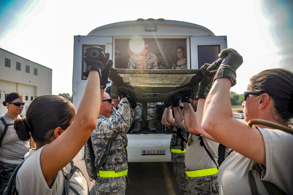 Airmen lift a litter onto a bus.