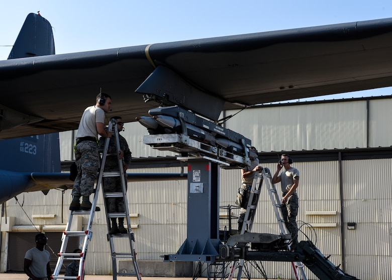 Airmen stand on ladders to make sure the loading bombs are aligned correctly.
