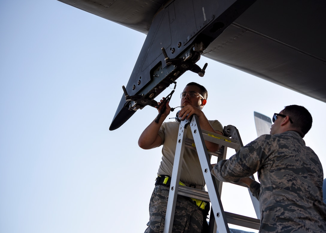 An Airman cuts wires on a bomb rack to set it up for a different kind of bomb.