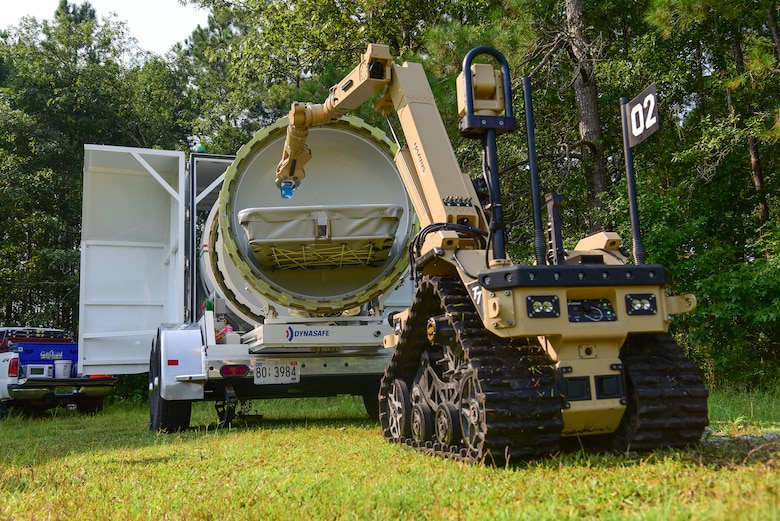 The Harris T7, a remotely operated ordnance disposal robot, places a liquid-filled vile in an explosion containment unit during the 2018 Eastern National Robotics Rodeo, Aug. 14, 2018, at Joint Base Charleston, S.C.