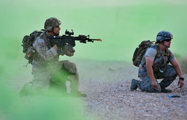 "Staff Sgt. Juan Hinojosa, 99th Security Forces Squadron military working dog handler and Erik, 99th SFS MWD, respond to a simulated ""live-fire"" scenario during a training exercise Aug. 8, 2018, at Nellis Air Force Base, Nev. This portion of the training was to test the dog's reaction to the sound of live gunfire and explosives while also testing how their handler would react to the situation. (U.S. Air Force Photo by Airman 1st Class Haley Stevens)"