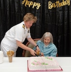 Capt. Maryann Mattonen (left), Navy Medicine Training Support Center commanding officer, and Blondina Porter cut Porter's  birthday cake together with a Navy officer ceremonial sword at the San Antonio Brookdale Assisted Living Facility to wish the World War II Navy Nurse a happy 100th birthday Aug. 15.