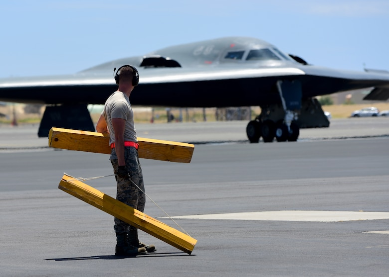A U.S. Air Force maintenance technician from Whiteman Air Force Base, Missouri, prepares to place wheel chocks on a B-2 Spirit at Joint Base Pearl Harbor-Hickam, Hawaii, Aug. 15, 2018. B-2s regularly rotate through the Indo-Pacific to conduct routine air operations, which integrate capabilities with key regional partners and demonstrate U.S. commitment to peace and stability in the region. These operations are in support of the U.S. Strategic Command's Bomber Task Force deployment. (U.S. Air Force photo by Staff Sgt. Danielle Quilla)