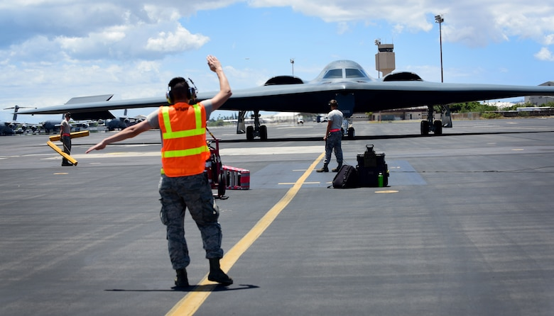 A U.S. Air Force maintenance technician from Whiteman Air Force Base, Missouri, marshals a B-2 Spirit at Joint Base Pearl Harbor-Hickam, Hawaii, Aug. 15, 2018. B-2s regularly rotate through the Indo-Pacific to conduct routine air operations, which integrate capabilities with key regional partners and demonstrate U.S. commitment to peace and stability in the region. These operations are in support of the U.S. Strategic Command's Bomber Task Force deployment. (U.S. Air Force photo by Staff Sgt. Danielle Quilla)