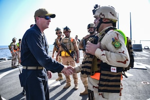 U.S. Navy and Coast Guard sailors discuss an exercise with Kuwaiti sailors.