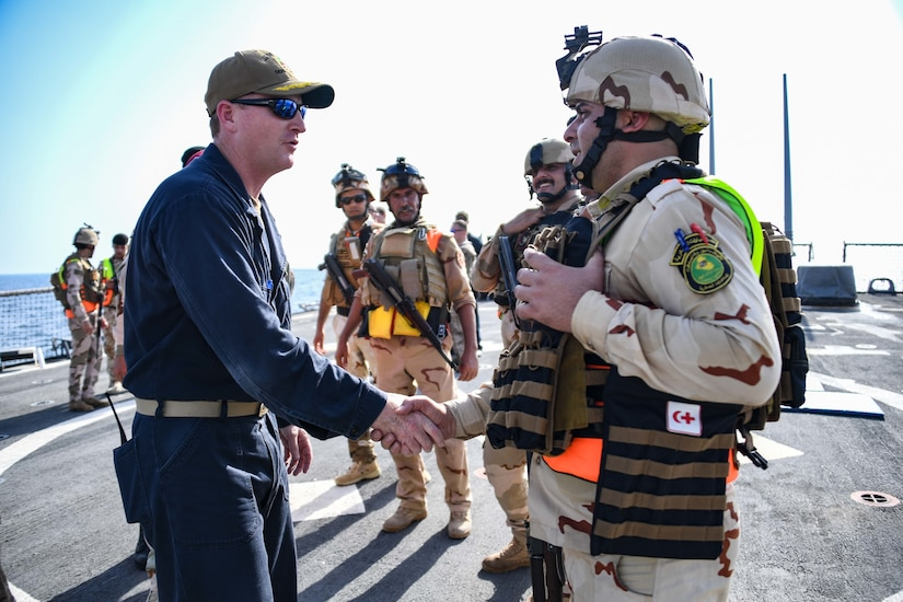 180814-N-RM440-2548 ARABIAN GULF (August 14, 2018) Cmdr. Russ Moore, guided-missile destroyer USS The Sullivans (DDG 68) commanding officer, left, shakes hands with a member of the Iraqi visit, board, search and seizure team during a trilateral exercise with Iraq and Kuwait. The exercise is a surface engagement between the U.S. Navy and Coast Guard and the Iraqi and Kuwaiti navies focused on improving proficiency in maritime security tactics to help ensure the freedom of navigation throughout the U.S. 5th Fleet area of operations (U.S. Navy photo by Mass Communication Specialist 2nd Class Samantha P. Montenegro/Released)