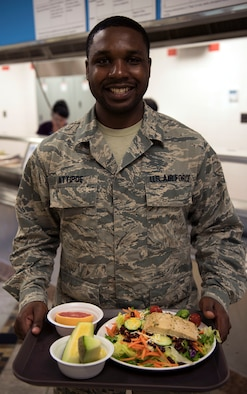 U.S. Air Force Senior Airman Francis Attipoe, 51st Force Support Squadron food shift leader, gets a healthy and nutritious meal from the House dining facility at Osan Air Base, Republic of Korea Pacific, Aug. 16, 2018. Osan started a new initiative, Food First!, to promote a healthier lifestyle and educate active duty military members about nutrition and safe supplement use. (U.S. Air Force graphic by Staff Sgt. Alexander Karnafel)
