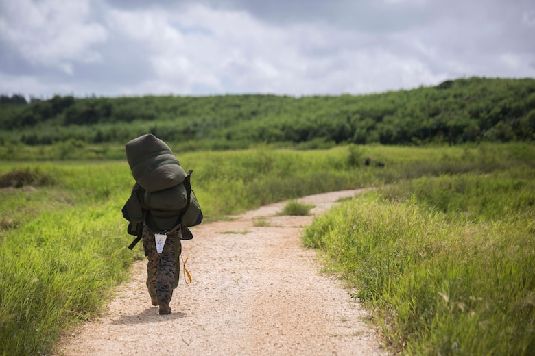 Cpl. Daniel Mehaffey carries his gear to the rendezvous point after parachuting 10,000 feet during parachute training operations Aug. 13, 2018 at Ie Shima, Okinawa, Japan. Landing Support Company completed parachute and air delivery training to ensure Marines maintain proficiency and meet required training hours. Mehaffey, a parachute rigger with Air Delivery Platoon, LS Co., 3rd Transportation Support Battalion, is a native of Warminster, Pennsylvania. (U.S. Marine Corps photo by Lance Cpl. Jamin M. Powell)