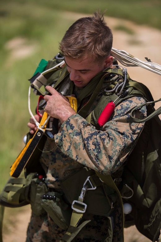 Cpl. Daniel Mehaffey removes his gear after jumping out of a CH-53E Super Stallion during parachute training operations Aug. 13, 2018 at Ie Shima, Okinawa, Japan. Landing Support Company completed parachute and air delivery training to ensure Marines maintain proficiency and meet required training hours. Mehaffey, a parachute rigger with Air Delivery Platoon, LS Co., 3rd Transportation Support Battalion, is a native of Warminster, Pennsylvania. (U.S. Marine Corps photo by Lance Cpl. Jamin M. Powell)