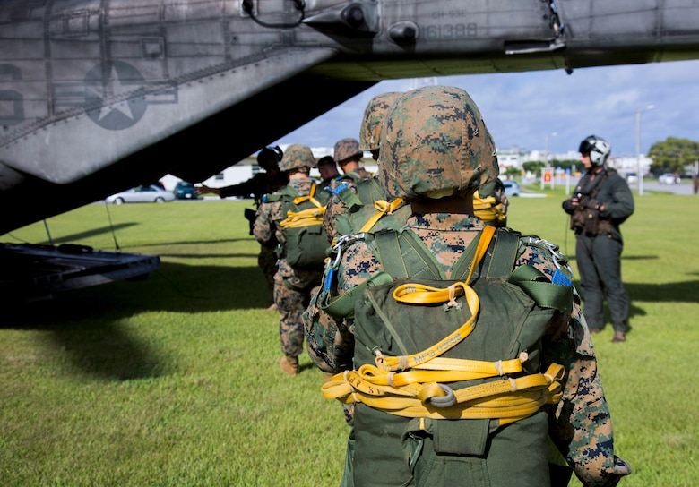 Marines with Landing Support Company, 3rd Transportation Support Battalion, 3rd Marine Logistics Group, board a CH-53E Super Stallion helicopter during parachute and air delivery training operations Aug. 14, 2018 at Ie Shima, Okinawa, Japan. The training consisted of low-level static line and military free fall jumps at 10,000 feet in order to keep the Marines proficient as parachute rigger/air delivery specialists. (U.S. Marine Corps photo by Cpl. Isabella Ortega)