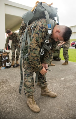 Lance Cpl. Connor Marrow straps on his MC-6 parachute in preparation for his low-level static jump during parachute and air delivery training operations Aug. 14, 2018 at Ie Shima, Okinawa, Japan. The training consisted of low-level static line and military free fall jumps at 10,000 feet in order to keep the Marines proficient as parachute riggers and air delivery specialists. Marrow, a native of Philadelphia, Pennsylvania, is a parachute rigger and air delivery specialist with Landing Support Company, 3rd Transportation Support Battalion, 3rd Marine Logistics Group. (U.S. Marine Corps photo by Cpl. Isabella Ortega)