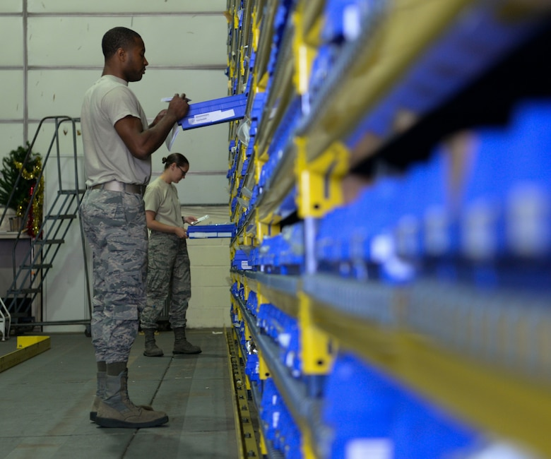 U.S Air Force Airman 1st Class Jimmy Ogletree, 100th Logistics Readiness Squadron aircraft parts store journeyman, front, and Staff Sgt. Morgan Petter, 100th LRS APS supervisor find aircraft parts for an order request at RAF Mildenhall, England, Aug. 8, 2018. The APS supplies the aircraft with mobility readiness spare part kits. Each package is tailored to support an aircraft for the first 30 days of a deployment. (U.S. Air Force photo by Airman 1st Class Alexandria Lee)