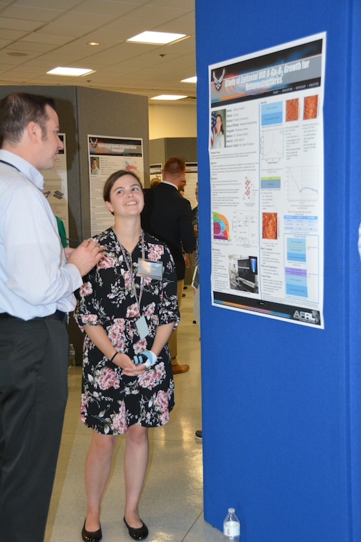 Ashley Wissel, Purdue University undergraduate student, displays her work performed over the summer at a poster session in the Air Force Research Laboratory Materials and Manufacturing Directorate attended by leadership, mentors and colleagues. (U.S. Air Force photo/Dave Dixon)