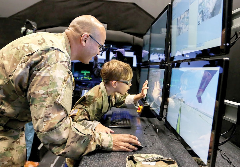Army Chief Warrant Officer 3 Saul Mulholland, 3rd Assault Helicopter Battalion, 4th Aviation Regiment, shows Carson Raulerson how flight instructors can control environmental variables for pilots training on the Black Hawk simulator at Fort Carson, Colo. Army photo by Sgt. Anthony Bryant