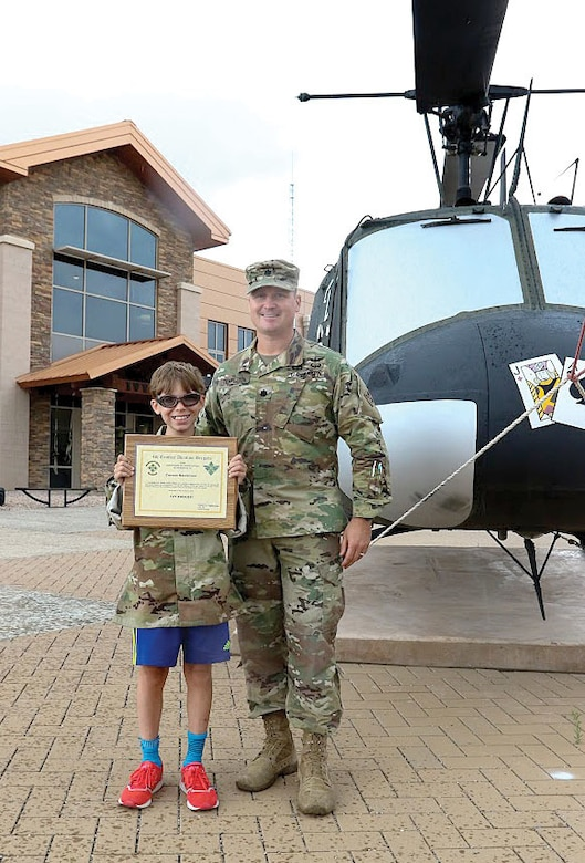 Army Lt. Col. Steven Templeton, commander of the rear detachment of the 4th Combat Aviation Brigade, 4th Infantry Division, presents Carson Raulerson with a certificate of appreciation at Fort Carson, Colo. Army photo by Sgt. Anthony Bryant