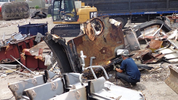A scrap contractor employee uses a torch to cut pieces of a large work boat even smaller.