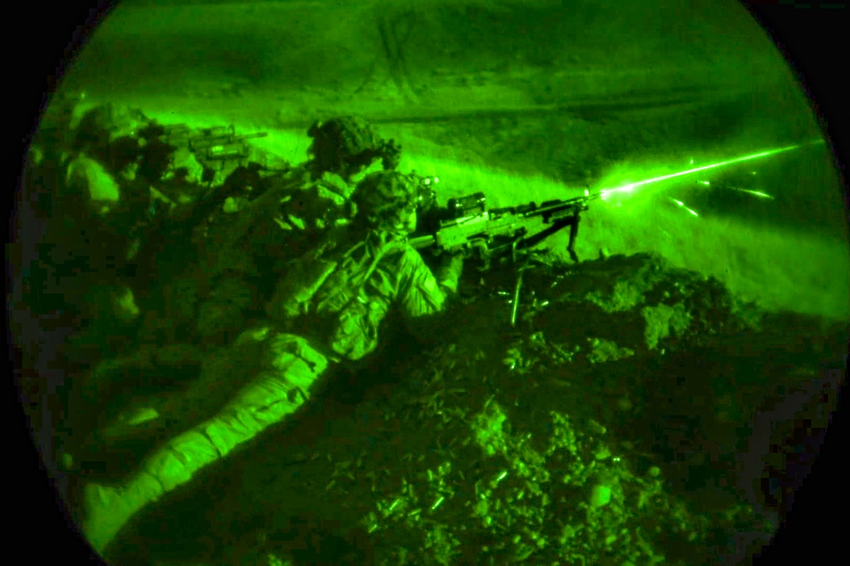 A soldier fires a weapon from a prone position at night.