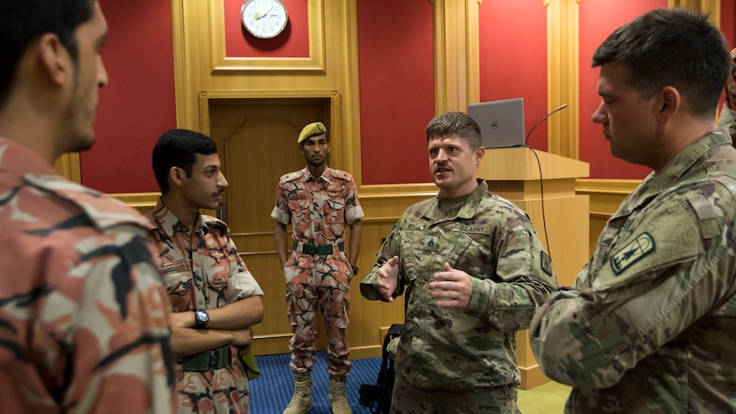 U.S. Army Staff Sgt. Christopher Reitz, a team leader, and U.S. Army Capt. Ken Ginther, the officer in charge both assigned to the 157th Military Engagement Team, Wisconsin Army National Guard, attached to U.S. Army Central, speak with soldiers from the Royal Army of Oman's Border Guard Brigade about best practices to use while protecting a border from smuggling at an engagement held between USARCENT and Oman's Border Guard Brigade in Haima, Oman, Aug. 6, 2018. Theater collaboration activities such as this engagement allow each force to learn new border security methods and techniques from each other.