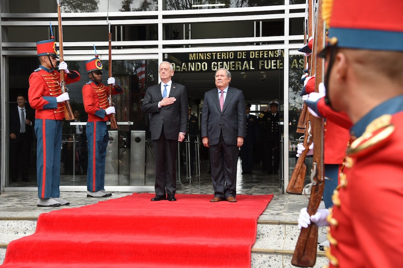 Defense Secretary James N. Mattis and Colombian Defense Minister Guillermo Botero stand at attention.