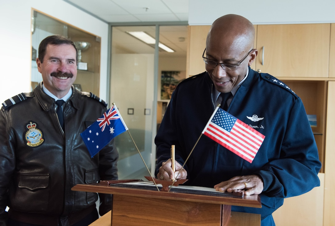 Gen. CQ Brown, Jr., Pacific Air Forces commander, signs a guest book before an office call with Air Marshal Leo Davies (left), Royal Australian Air Force (RAAF) chief of Air Force, at the Russell offices, Canberra, Australia, Aug. 10, 2018. His first trip to the region since taking command on July 26, 2018, Brown met with key defense and military leaders in Canberra and RAAF Bases Williamtown, Tindal and Darwin to see first-hand the strength of the U.S.-Australia alliance and discuss opportunities to ensure a free and open Indo-Pacific region. (U.S. Air Force photo by Staff Sgt. Hailey Haux)