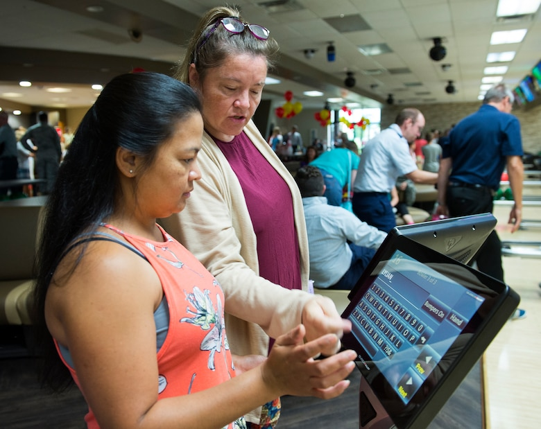 Deloris Wurn helps Jesusa Burdick with the new electronic scoring system at the Wright-Patterson Air Force Base, Ohio, Bowling Center Aug. 13, 2018, shortly after the ribbon cutting for the centers grand reopening.