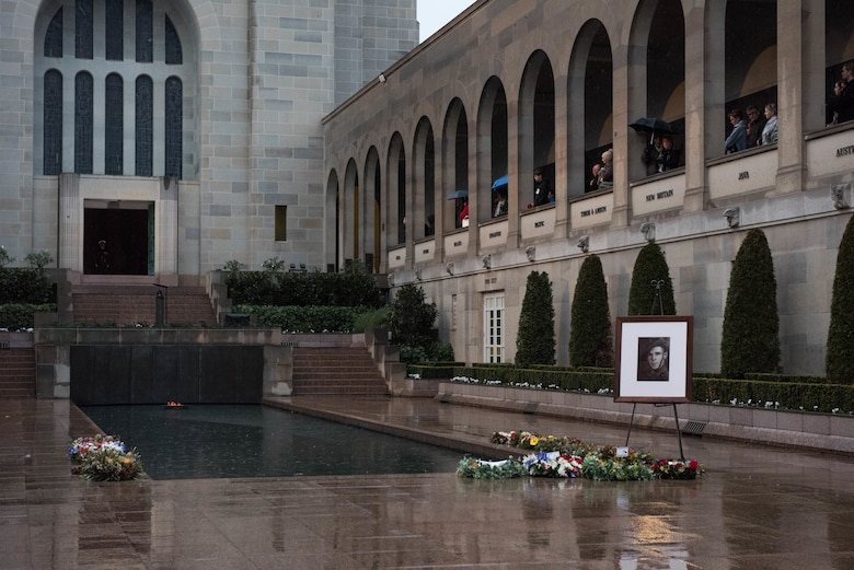 "A portrait of Pvt. Robert Young of the Australian Army sits at the base of the pool of remembrance at the Australia War Memorial in Canberra, Australia, Aug. 11, 2018. Young fought in World War II and died March 21, 1944. Gen. CQ Brown, Jr., Pacific Air Forces commander, participated in Young's ""Last Post"" ceremony, honoring his service and sacrifice, further demonstrating the strength of the U.S.-Australian alliance.   (U.S. Air Force photo by Staff Sgt. Hailey Haux)"