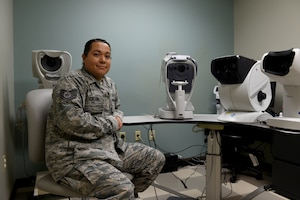 Photo of Staff Sgt. Ivonn Denton sitting in front of eye exam machines.