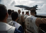 """Maritime Self-Defense Force officers and U.S. Navy officers watch an F/A-18E Super Hornet, assigned to the """"Dambusters"""" of Strike Fighter Squadron (VFA) 195, land on the aircraft carrier USS Ronald Reagan (CVN 76) during flight operations. Ronald Reagan is forward-deployed to the U.S. 7th Fleet area of operations in support of security and stability in the Indo-Pacific region."""