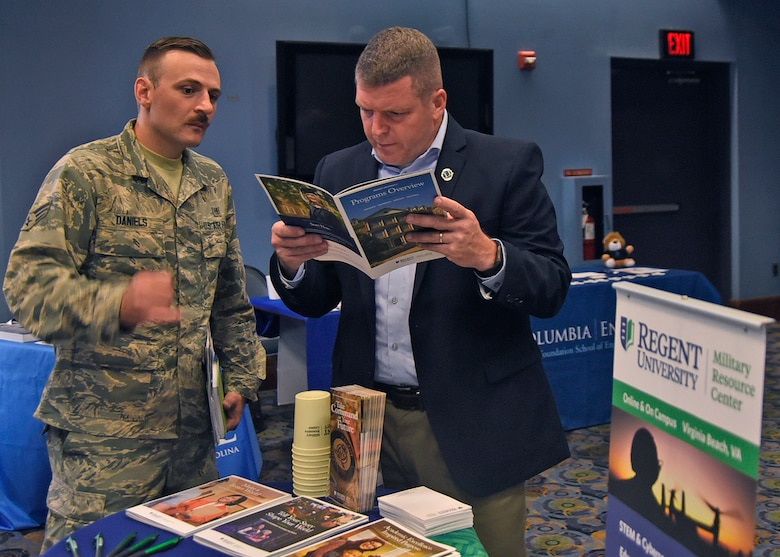 Senior Airman Alan Daniels, 11th Medical Group cardiopulmonary lab technician, speaks with Bill Snow from Regent University during an education fair at Joint Base Andrews, Md., Aug. 16, 2018. At each booth, prospective students learned about topics such as admissions processes, degree programs and school offerings. (U.S. Air Force photo by Senior Airman Abby L. Richardson)