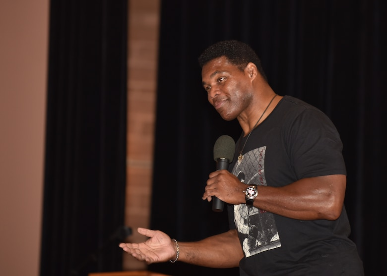Herschel Walker, former professional football player, speaks to 90th Missile Wing Airmen Aug. 14, 2018, during his visit to F.E. Warren Air Force Base, Wyo. Walker's speech encouraged Airmen to be resilient and never give up even through life's toughest times. (U.S. Air Force photo by Airman 1st Class Braydon Williams)
