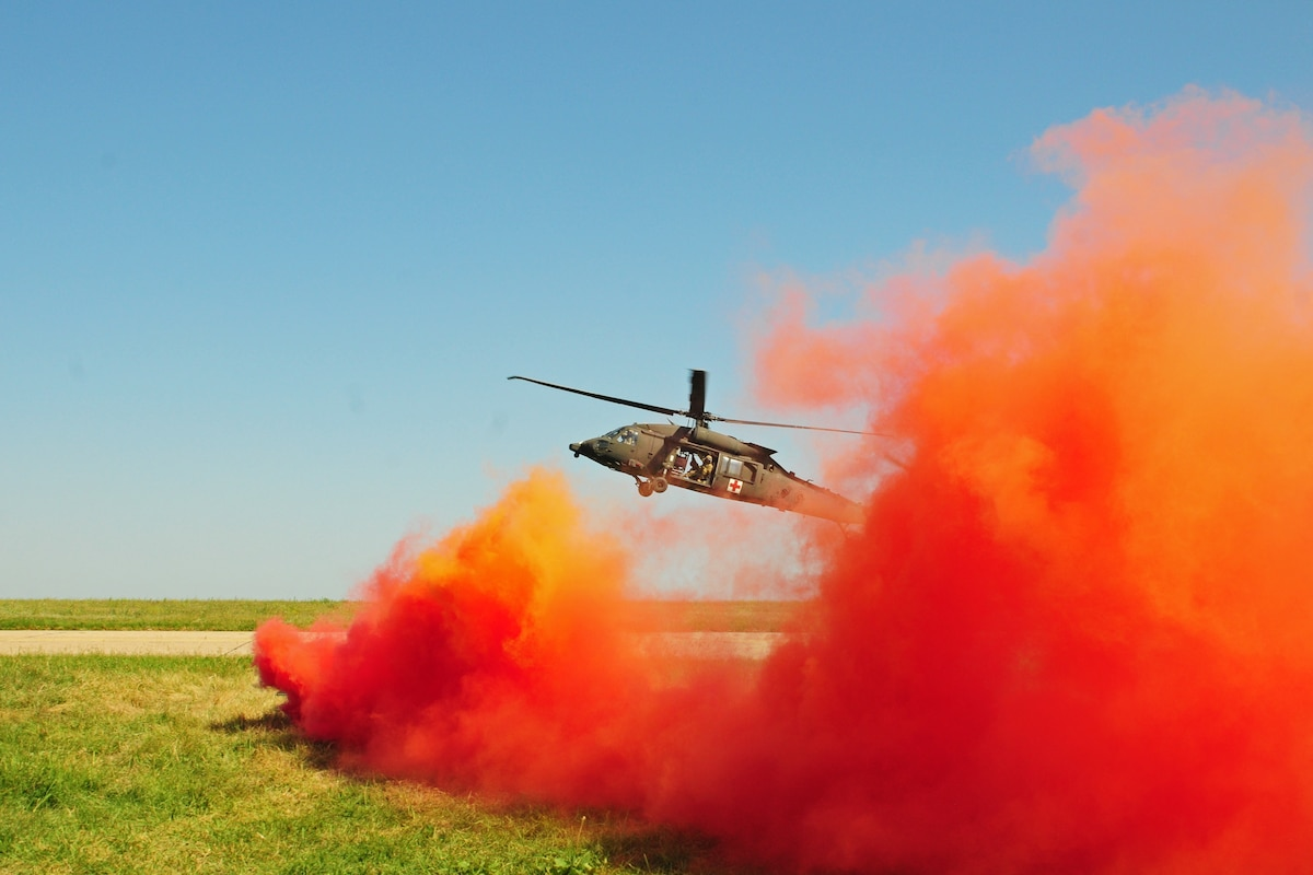 A helicopter takes off surrounded by red smoke.