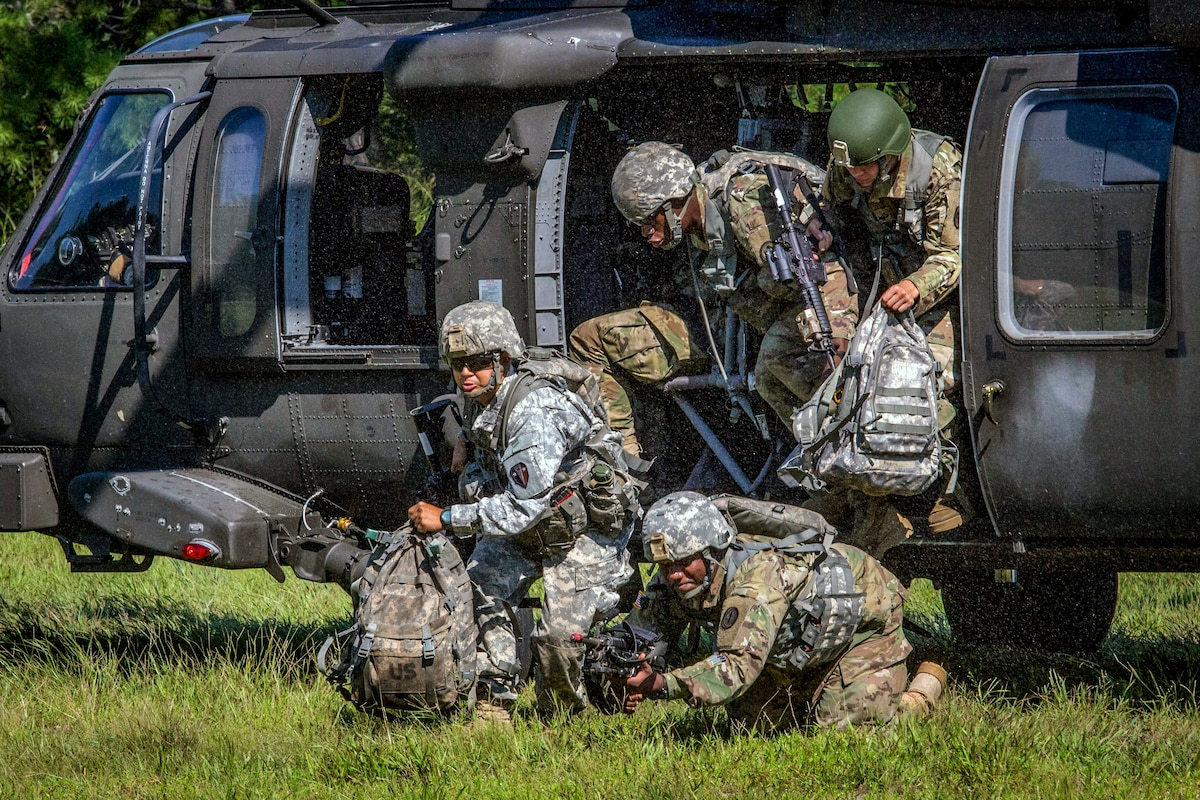 Soldiers exit a helicopter in a field.