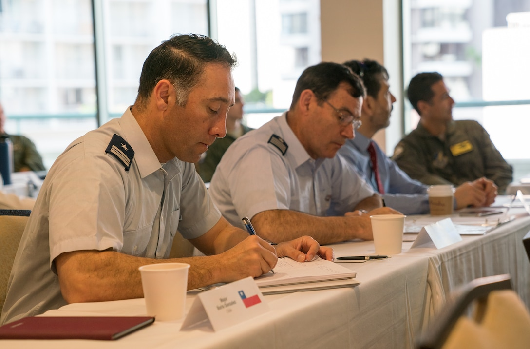 Chilean air force Maj. Boris Gonzalez (left) and Chilean air force Col. Sergio Figueroa (right) take notes during the resource and risk management presentation of the Asia-Pacific Aviation Safety Subject Matter Expert Exchange (APASS) in Honolulu, Hawaii, Aug. 14, 2018. APASS allows partner nations to discuss aviation safety practices and devise solutions to challenges faced by the various air forces. (U.S. Air Force photo by Staff Sgt. Daniel Robles)