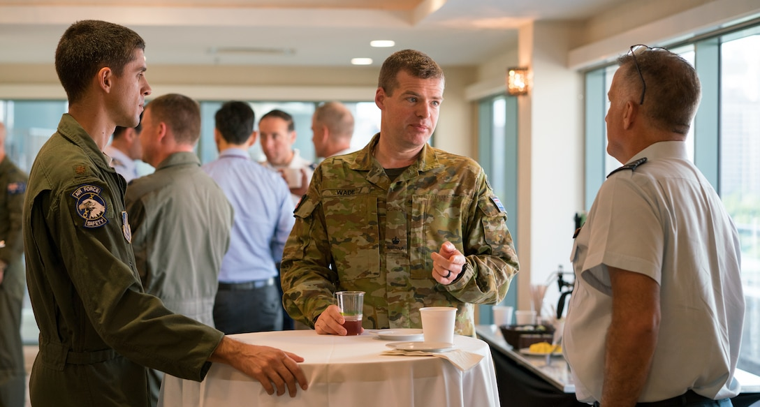 U.S. Air Force Maj. Eric Johnston (left), Royal Australian air force Maj. David Wade (center) and Royal Canadian air force Col. John Alexander (right) socialize during the Asia-Pacific Aviation Safety Subject Matter Expert Exchange (APASS) in Honolulu, Hawaii, Aug. 14, 2018. APASS allows partner nations in the Indo-Pacific to discuss aviation safety practices and devise solutions to challenges faced by the various air forces. (U.S. Air Force photo by Staff Sgt. Daniel Robles)