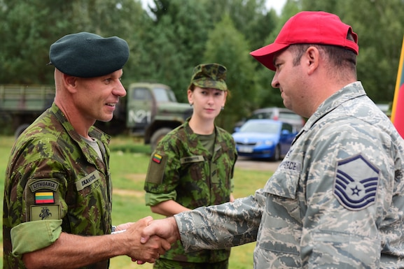 Lithuanian Maj. Kestutis Cekavicius (left), training area commander at the Brigadier General Kazio Veverskis Training Grounds, Kazlu Ruda, Lithuania, thanks U.S. Air Force Master Sgt. Andrew Hikes, 201st Rapid Engineer Deployable Heavy Operational Repair Squadron Engineers non-commissioned officer in charge of Rotation 2, during a ceremony on the rotation's last day in Lithuania, Aug. 13, 2018. This is the second of four 201st RHS rotations traveling to Lithuania completing deployment for training and constructing a military air-to-ground training range to be used by Lithuanian and other NATO forces. (U.S. Air National Guard photo by Tech. Sgt. Claire Behney/Released)