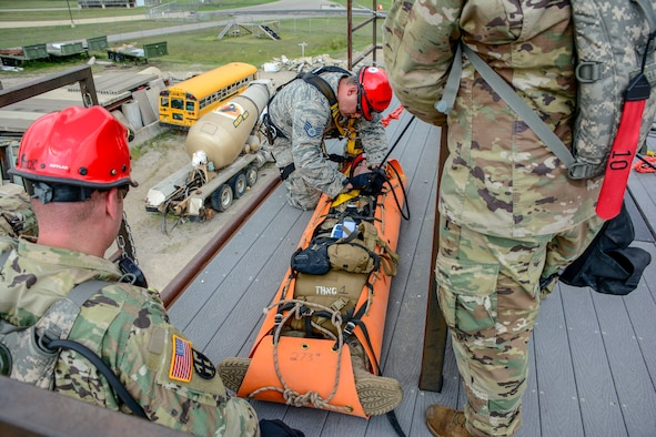 Joint military members with the Wisconsin Chemical, Biological, Radiological, Nuclear and High Yield Explosive Enhanced Response Force Package Medical Group prep a soldier for a sked drop over the side of a building as part of the 2018 External Evaluation exercise at Volk Field Air National Guard Base, Aug. 16, 2018. The ExEval is conducted as a way to re-validate the WI CERFP to perform its CBRN Response Enterprise mission in support of the State and Nation.(U.S. Air National Guard photo by Tech. Sgt. Mary E. Greenwood)