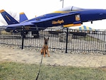 A police K-9 sits in front of a grounded US Navy Blue Angels aircraft on display.