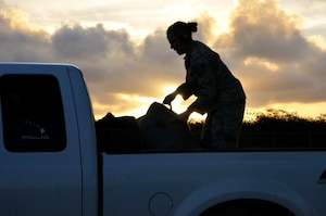 An airman stows luggage in a truck at twilight.