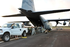 Service members from the Air National Guard and Navy Reserve unload equipment from a C-130 Hercules aircraft after arriving in Molokai, Hawaii, for Tropic Care Maui County 2018, Aug. 10, 2018. Tropic Care Maui County 2018 is a joint-service training mission offering no cost medical, dental, and vision services to people at six locations across Maui, Molokai and Lanai. Air National Guard photo by Air Force Staff Sgt. Lonnie Wiram