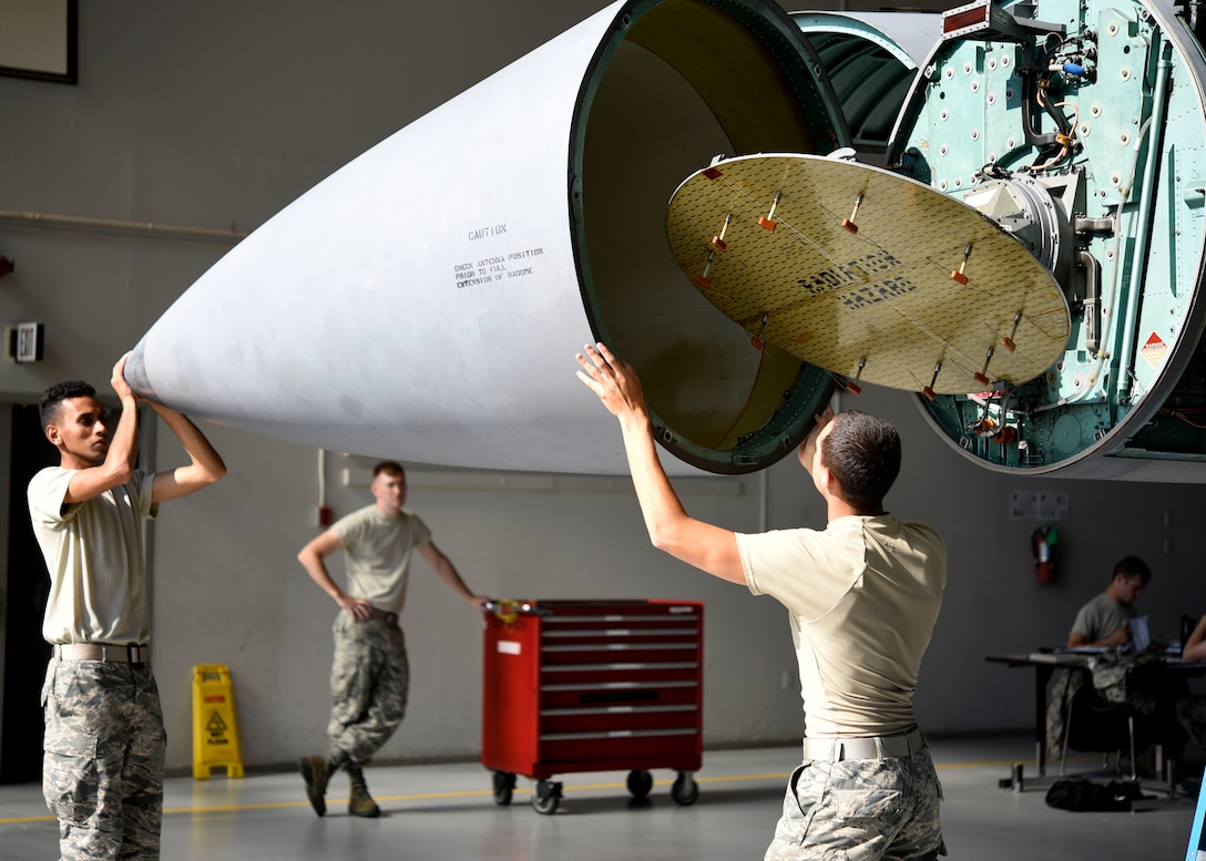 Airman Chris Hilton, left front, and Airman 1st Class Dominik Roeglin, right front, 362nd Training Squadron F-15 crew chief apprentice course students, open an F-15's nose at Sheppard Air Force Base, Texas, August 1, 2018. The radar used in the F-15 Fighting Falcon's at Sheppard are an A model. Older versions that are static, non-moving pieces. There are still some F-15s in service that use these A model radars, but everything is slowly progressing towards the fancier radars. (U.S. Air Force photo by Airman 1st Class Pedro Tenorio)